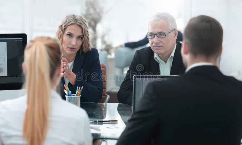 Gruppe überzeugte Teilhaber, die Papier bei der Sitzung besprechen lizenzfreie stockfotos
