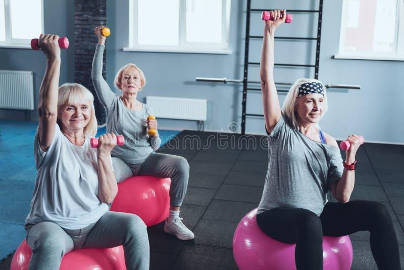 Gruppe aktive ältere Damen, die mit Dummköpfen an der Turnhalle ausbilden lizenzfreies stockfoto
