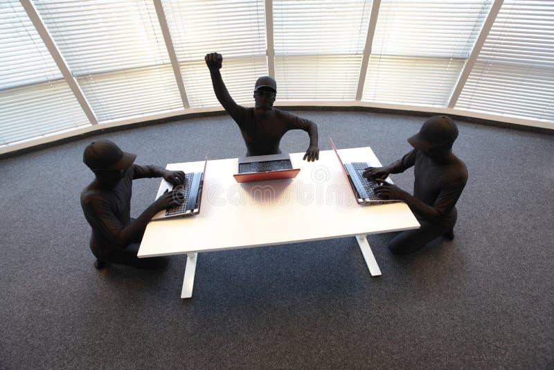 Gruppe anonyme Häcker, die mit Computern im Büro arbeiten lizenzfreie stockfotos