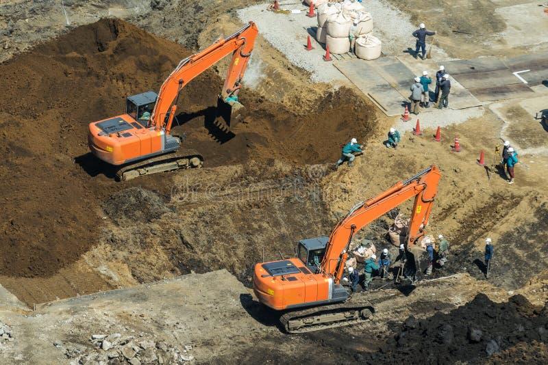Gruppe Arbeitskräfte, die an Baustelle mit Bagger arbeiten stockfotografie