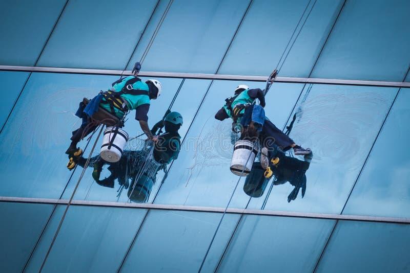 Gruppe Arbeitskräfte, die Fensterservice am hohen Aufstiegsgebäude säubern stockbilder