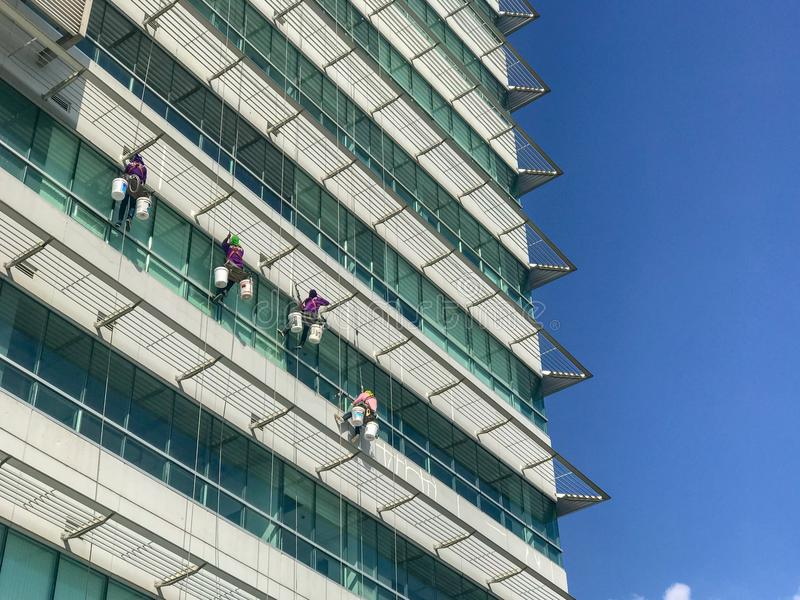 Gruppe Arbeitskräfte, die Fensterservice am hohen Gebäude säubern stockfotos