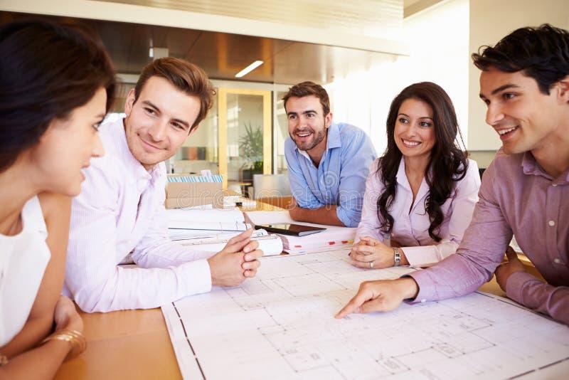Gruppe Architekten, die Pläne im modernen Büro besprechen lizenzfreie stockfotografie