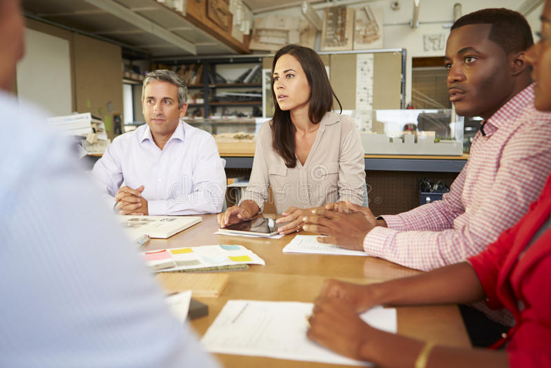 Gruppe Architekten, die um die Tabelle hat Sitzung sitzen lizenzfreie stockbilder