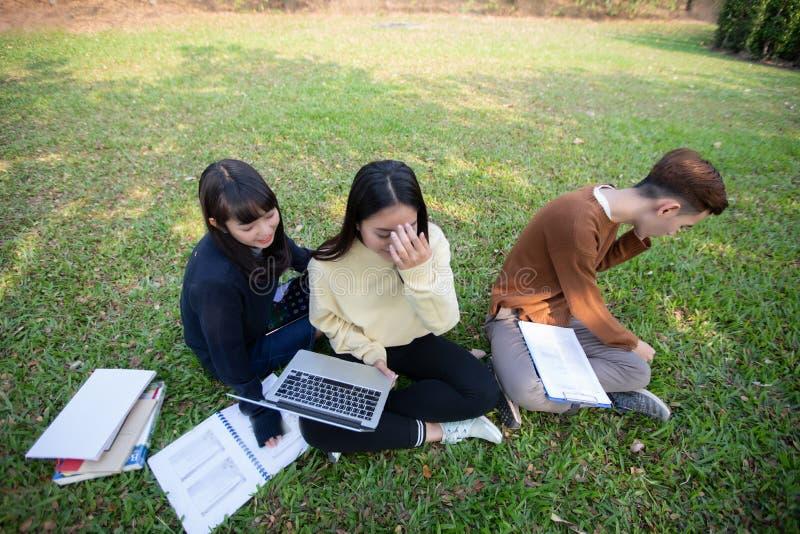 Gruppe asiatisches Sitzen der Hochschulstudenten auf dem grünen Gras W lizenzfreies stockbild