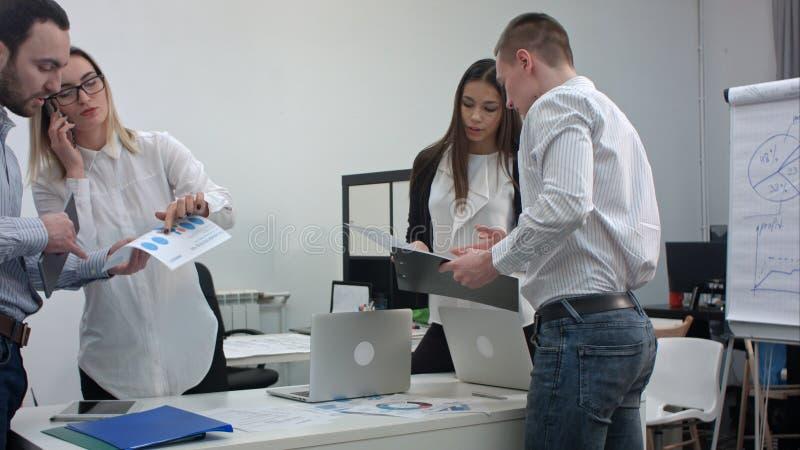 Gruppe Büroangestellte mit den Diagrammen, die für Geschäftsdarstellung sich vorbereiten stockfotografie