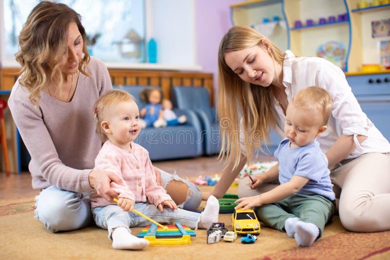 Gruppe Babykleinkinder, die mit bunten pädagogischen Spielwaren und Müttern im Kindertagesstättenraum spielen lizenzfreie stockbilder