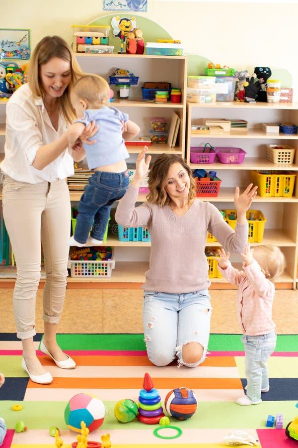 Gruppe Babykleinkinder, die mit bunten pädagogischen Spielwaren zusammen mit Müttern im Kindertagesstättenraum spielen lizenzfreie stockfotos