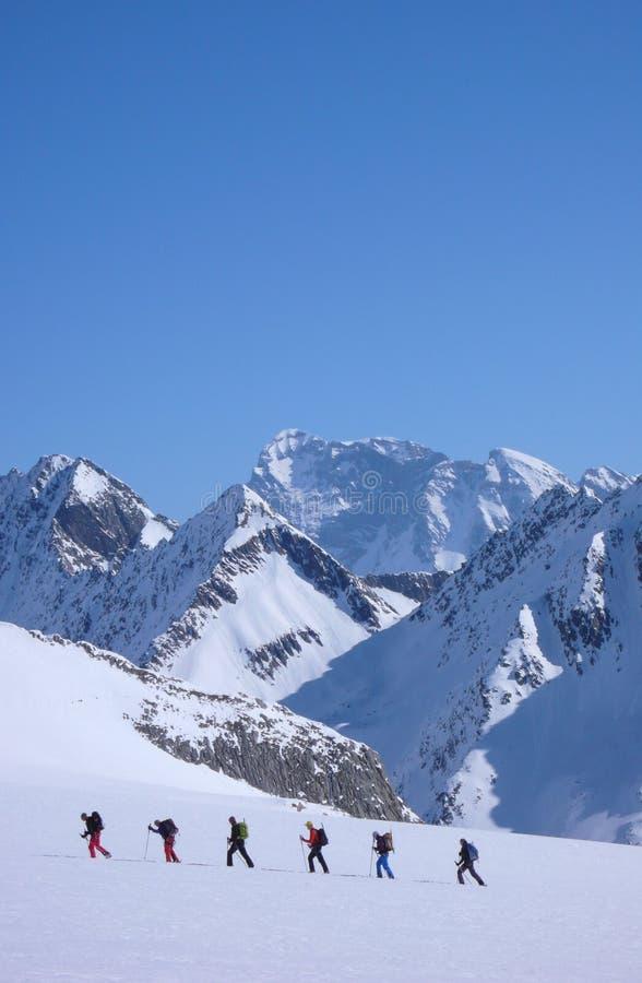 Gruppe backcountry Skifahrer, die einen Gletscher auf ihrer Weise zu einem hohen Gipfel in den Alpen kreuzen stockfotos