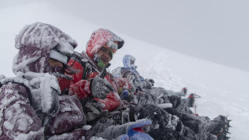 Gruppe Bergsteiger, die am Gipfel des Cotopaxi-Vulkans beim Warten auf den Schneesturm, um zu überschreiten, um anzufangen abzust lizenzfreies stockbild