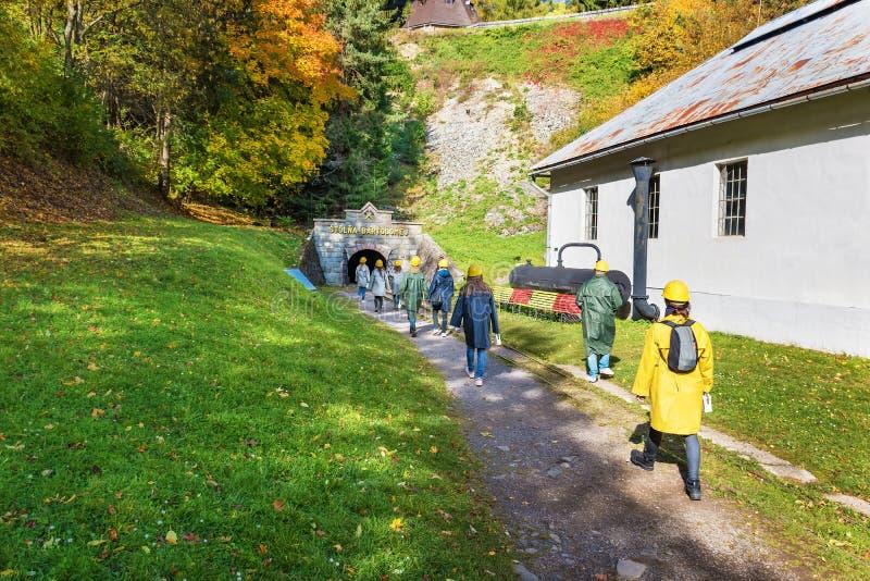 Gruppe Besucher gekleidet in einem Bergbaukaminsims, mit einem Sturzhelm und einem Laternenweg in Minenschacht lizenzfreie stockfotos