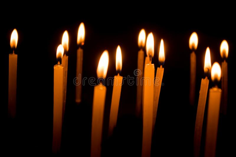 Gruppe brennende Kerzen in der Dunkelheit stockfotografie