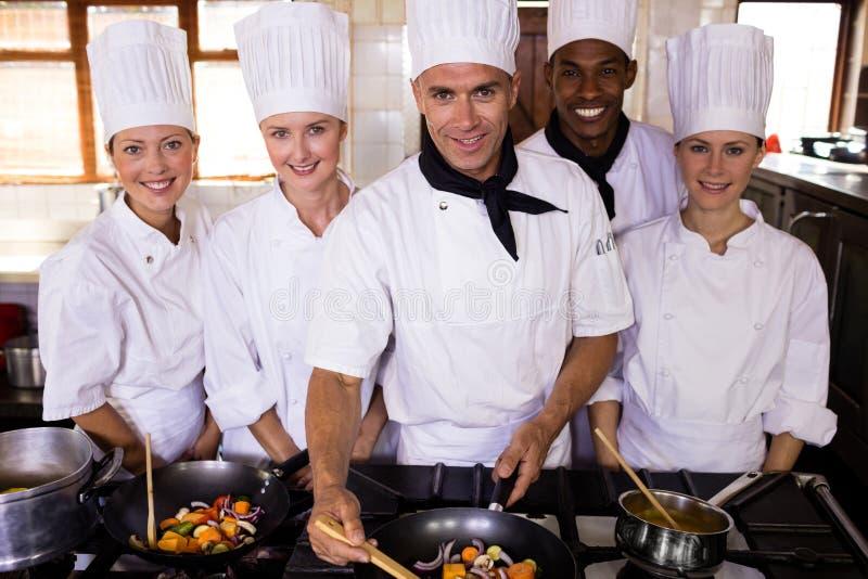 Gruppe Chefs, die Nahrung in der Küche zubereiten lizenzfreie stockfotos