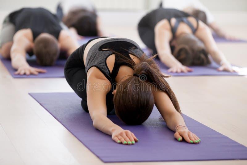 Gruppe der übenden Yogalektion der jungen sportlichen Leute, Kind-exerc lizenzfreies stockbild