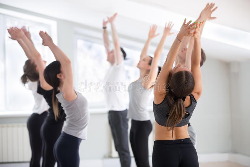 Gruppe der übenden Yogalektion der jungen sportlichen Leute, Tadas tuend stockfoto