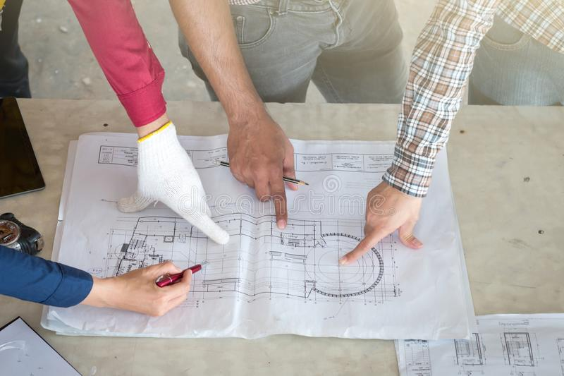Gruppe der Ingenieure, die den Entwurf auf dem Tisch prüfen und über das Bauprojekt sprechen mit Engagement für Erfolg bei lizenzfreie stockbilder