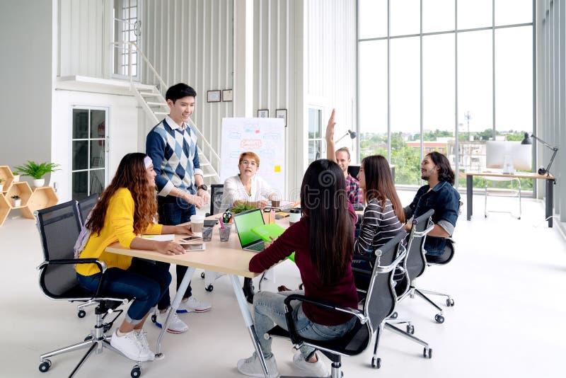 Gruppe der junger asiatischer kreativer Teamunterhaltung, -lächelns und -lachens gedanklich lösend, teilend oder auf Sitzung oder lizenzfreies stockbild