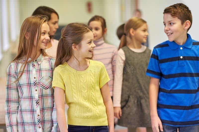 Gruppe der lächelnden Schule scherzt das Gehen in Korridor lizenzfreie stockfotografie