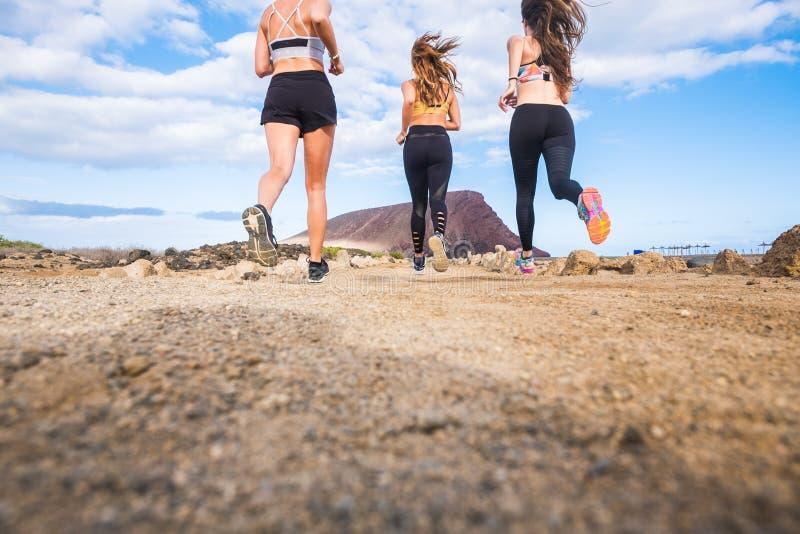 Gruppe der schönen hinteren Ansicht der Frauläufer, welche die Sporttätigkeit rüttelt in im Freien tun Berg im Hintergrund und ge stockfoto