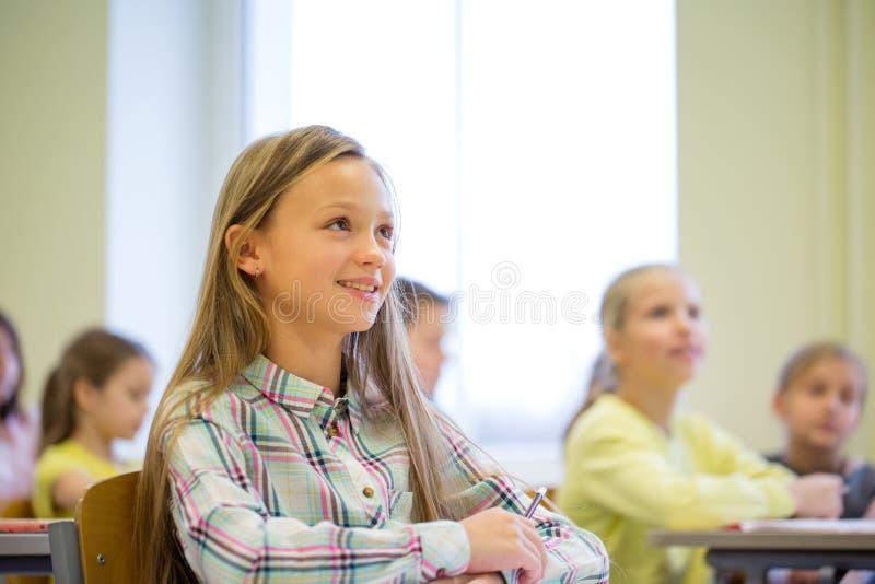 Gruppe der Schule scherzt mit Notizbüchern im Klassenzimmer stockbild