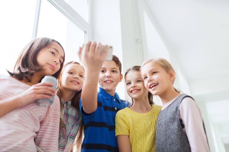 Gruppe der Schule scherzt mit Smartphone und Getränkedosen stockfoto