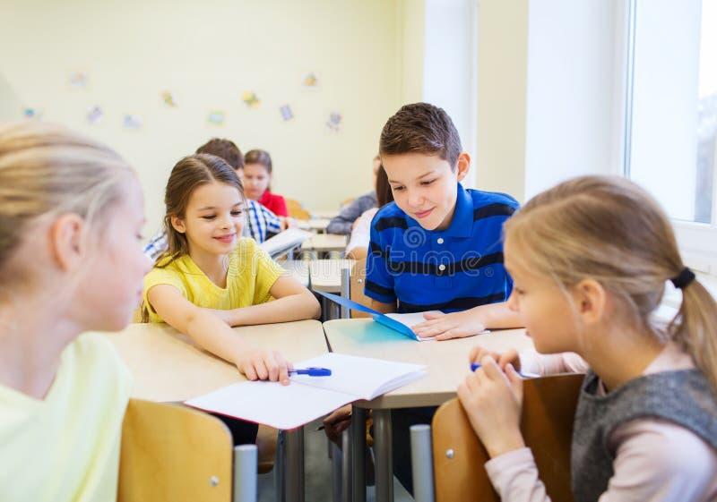 Gruppe der Schule scherzt Schreibenstest im Klassenzimmer stockbild