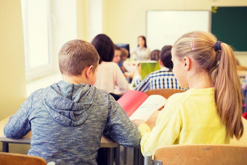Gruppe der Schule scherzt Schreibenstest im Klassenzimmer stockfotos