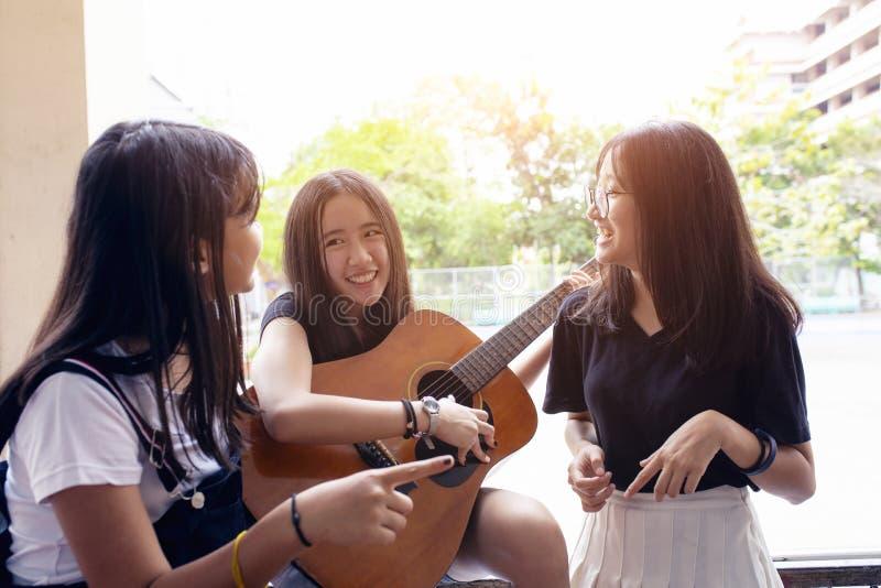 Gruppe des asiatischen Jugendlichen stehend im Freien, spanische Gitarre aus?bend und mit Gl?ckgef?hl tanzend lizenzfreies stockbild