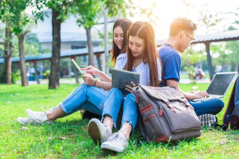 Gruppe des asiatischen Studenten, der Tablette und Laptop auf Gras verwendet stockfotos