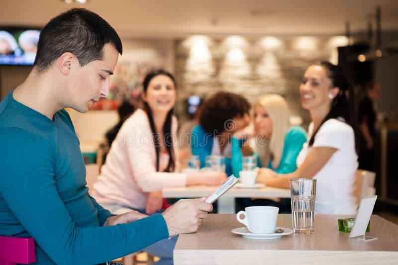 Gruppe des aufpassenden gutaussehenden Mannes des Mädchens im Café stockfoto