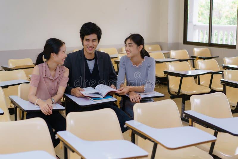 Gruppe des Buches mit drei Studenten Lesezusammen im Klassenzimmer stockfotografie