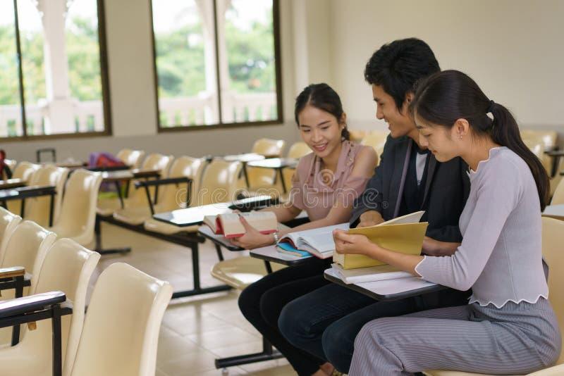 Gruppe des Buches mit drei Studenten Lesezusammen im Klassenzimmer stockfotos