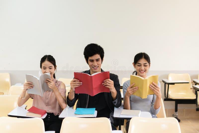 Gruppe des Buches mit drei Studenten Lesezusammen im Klassenzimmer lizenzfreie stockfotos