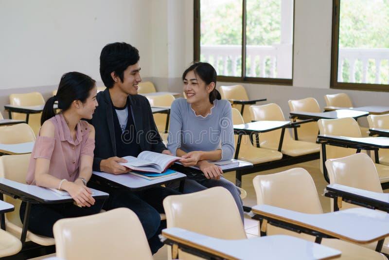 Gruppe des Buches mit drei Studenten Lesezusammen im Klassenzimmer stockbild