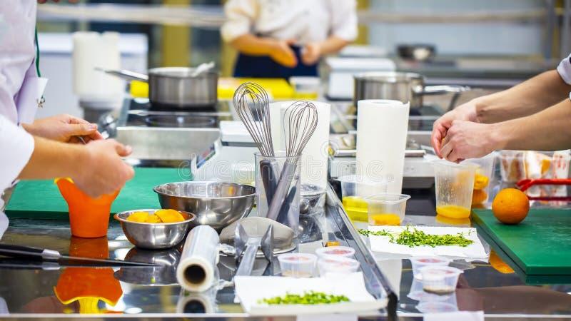 Gruppe des Chefs Lebensmittel in der Küche eines Restaurants zubereitend stockfotografie