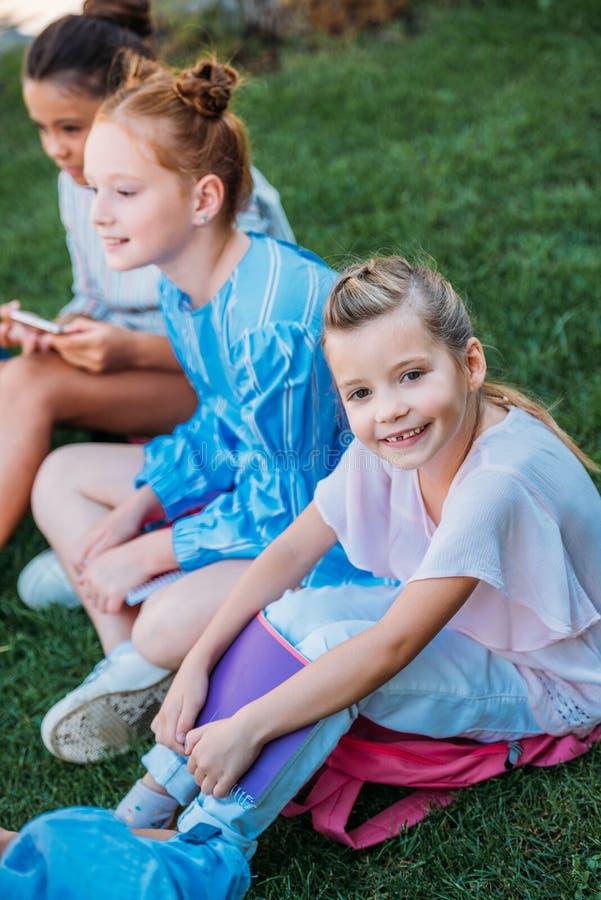 Gruppe des entzückenden Schulmädchensitzens stockfoto
