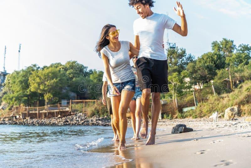 Gruppe des Freund-Laufs durch Wellen zusammen auf Strand-Ferien stockfoto