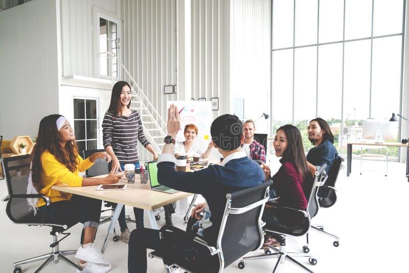 Gruppe des gemischtrassigen jungen kreativen Teams, das in der Sitzung am modernen Bürokonzept spricht, lacht und gedanklich löst lizenzfreie stockfotos