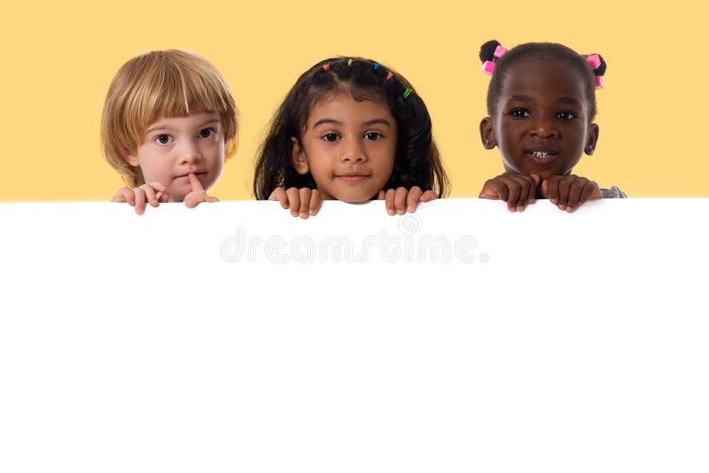 Gruppe des gemischtrassigen Kinderporträts mit weißem Brett stockbild