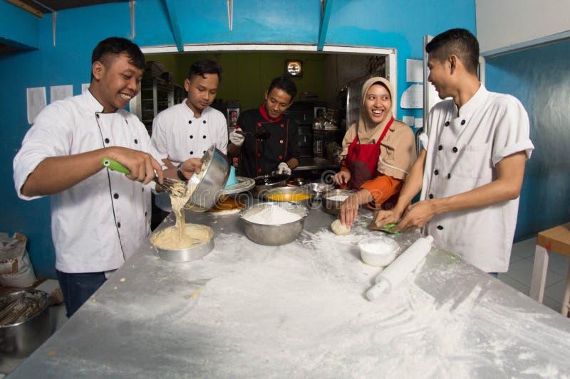 Gruppe des gl?cklichen jungen asiatischen Patissiers, der Teig mit Mehl, profesional Chef arbeitet an der K?che zubereitet lizenzfreies stockbild