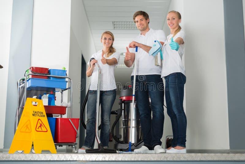 Gruppe des glücklichen jungen Hausmeisters Showing Thumbs Up stockfotografie