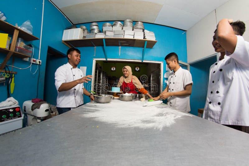 Gruppe des gl?cklichen jungen asiatischen Patissiers, der Teig mit Mehl, profesional Chef arbeitet an der K?che zubereitet lizenzfreies stockfoto