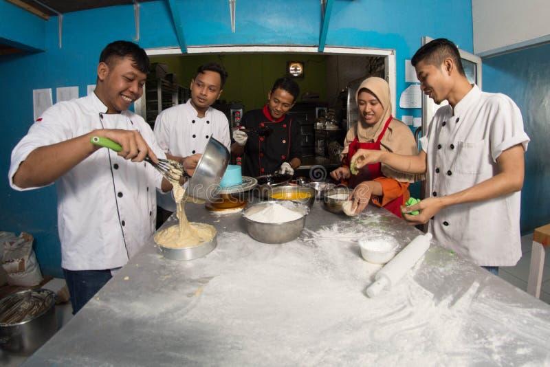 Gruppe des gl?cklichen jungen asiatischen Patissiers, der Teig mit Mehl, profesional Chef arbeitet an der K?che zubereitet lizenzfreie stockbilder