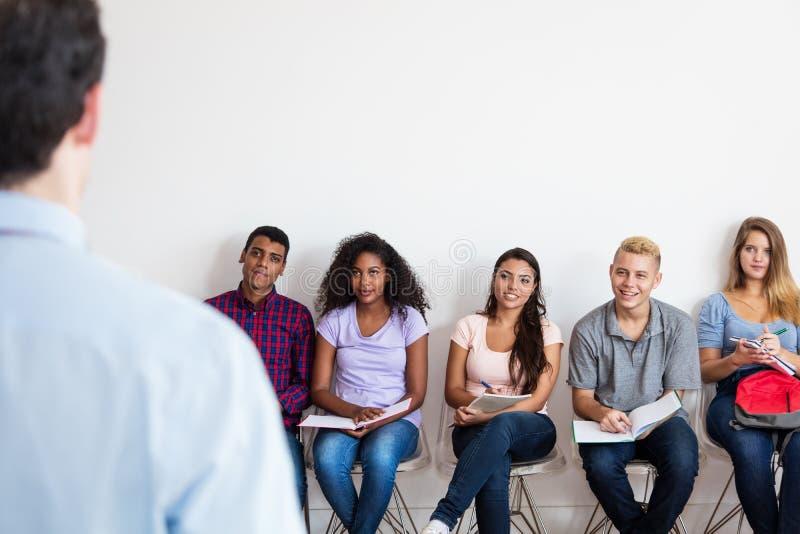 Gruppe des jungen erwachsenen Studenten, der auf Lehrer hört stockfotografie