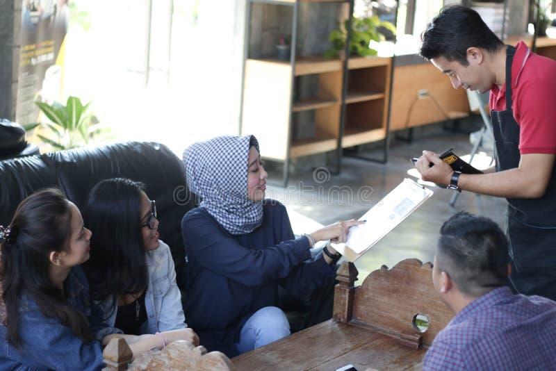 Gruppe des jungen glücklichen Freunds, der vom Menü bestellt, während Kellner die Aufträge am Café und am Restaurant schreiben lizenzfreie stockbilder