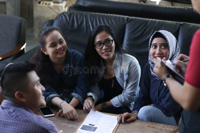 Gruppe des jungen glücklichen Freunds, der vom Menü bestellt, während Kellner die Aufträge am Café und am Restaurant schreiben lizenzfreies stockfoto