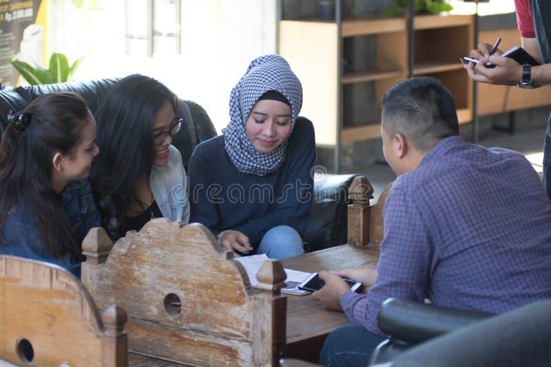 Gruppe des jungen glücklichen Freunds, der vom Menü bestellt, während Kellner die Aufträge schreiben stockfoto