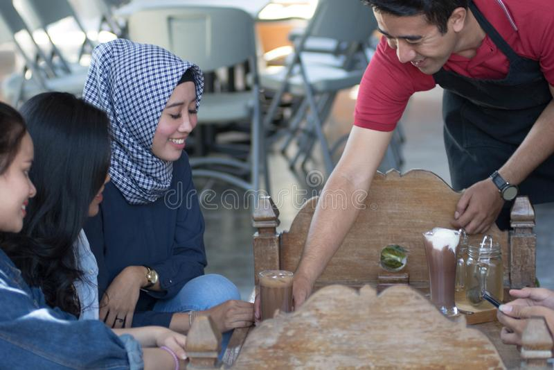 Gruppe des jungen glücklichen Freunds empfängt Nahrung und Getränk von den Kellnern und vom Server am Café und am Restaurant lizenzfreie stockfotografie
