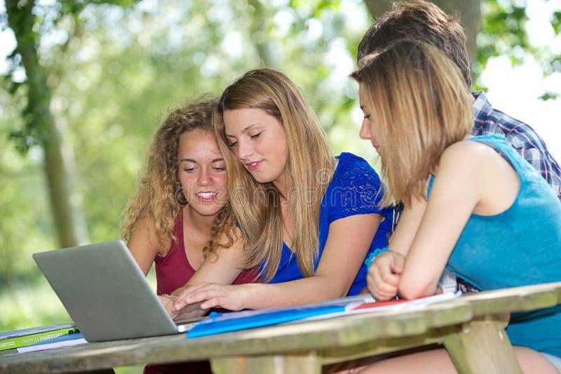 Gruppe des jungen Kursteilnehmers, der den Laptop im Freien verwendet stockfoto