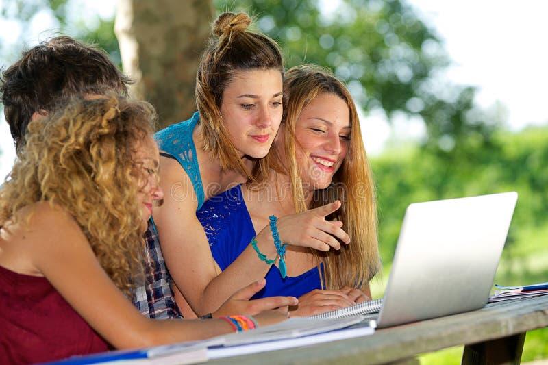 Gruppe des jungen Kursteilnehmers, der den Laptop im Freien verwendet stockfotografie